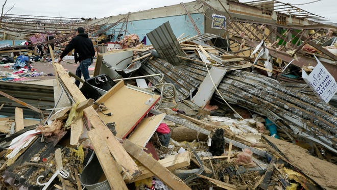 A man walks through rubble of the Vilonia Shopping Center in Vilonia, Ark., Wednesday, April 30, 2014. A tornado struck the town late Sunday.