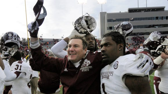 Mississippi State coach Dan Mullen, celebrates Mississippi State's 24-17 overtime victory over Arkansas with defensive back Nickoe Whitley  after their win in Little Rock, Ark., on Saturday, Nov. 23, 2013. (AP Photo/David Quinn)