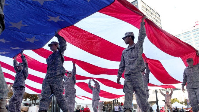 Members of Eastern High School's ROTC program carry a American flag during the UAW 862/Ford Motor Company Veterans Day Parade. November 11, 2013