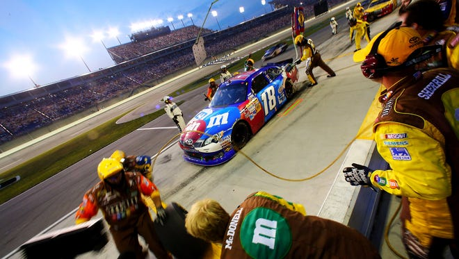 NASCAR Sprint Cup Series driver Kyle Busch makes a pit stop during the 2012 Quaker State 400 at Kentucky Speedway.