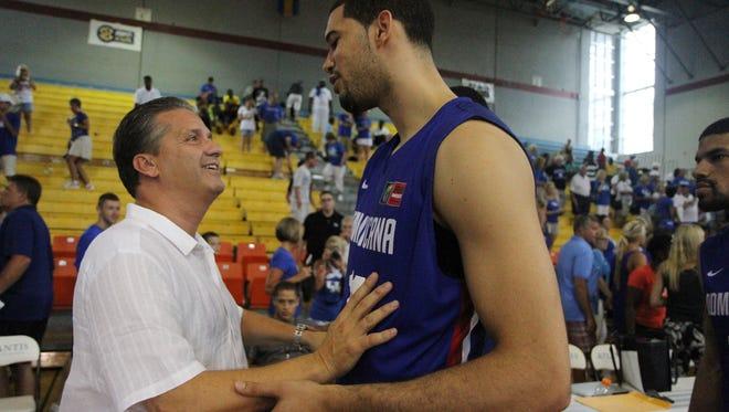 Kentucky head coach John Calipari greets former Kentucky player and Dominican Republic team member Eloy Vargas following the teams' exhibition game in Nassau, Bahamas. August 15, 2014.