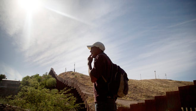 A man stands near the border fence outside Nogales, Sonora.