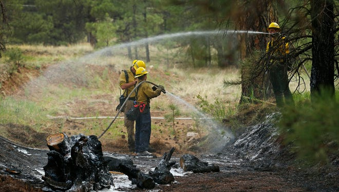 Flagstaff firefighters extinguish a spot fire on Mountain Dell Road on Sunday, May 25, 2014, near Flagstaff.