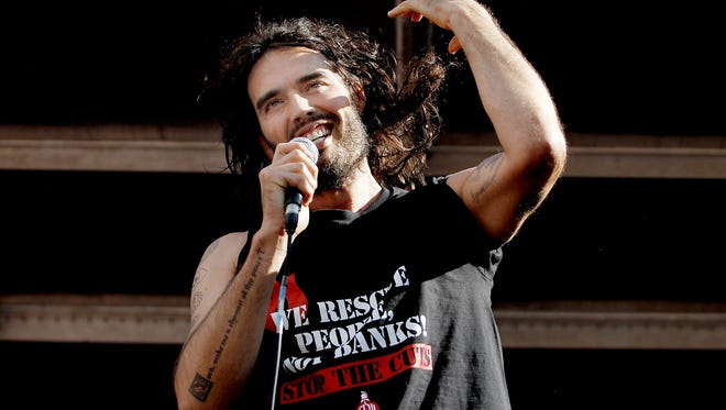 Comedian Russell Brand speaks to a crowd of thousands of demonstrators that gathered in Parliament Square, on June 21, 2014 in London, England.