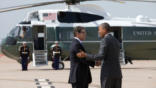 President Barack Obama is greeted by Texas Gov. Rick Perry as he arrives at Dallas/Fort Worth International Airport on July 9, 2014.