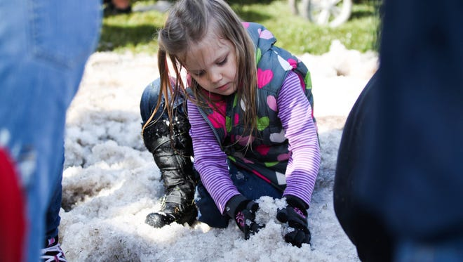Ember Haggerty plays in the snow at the Winter in July event at the Phoenix Zoo.