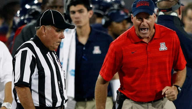 Arizona coach Rich Rodriguez talks with side judge Dave Cushman during the Wildcats' game against UNLV on Aug. 29 in Tucson.