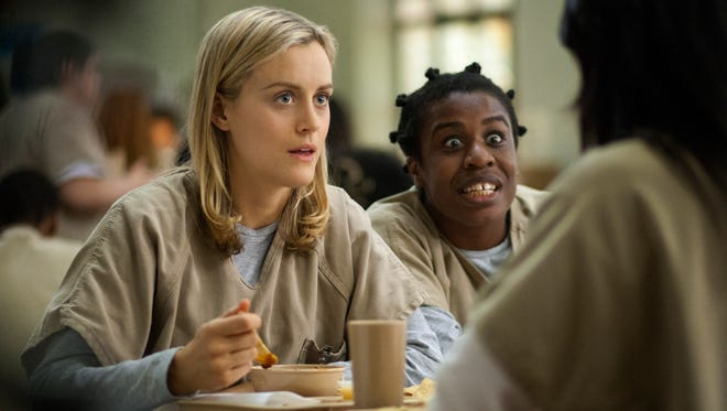 "This image released by Netflix shows Taylor Schilling, left, and Uzo Aduba in a scene from ""Orange Is the New Black."" Season two debuts on Netflix on June 6, 2014."