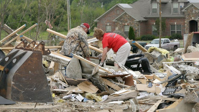 Milous Osier, left, and Jackie Foulkes look through debris at Vilonia Realty in Vilonia, Ark., Wednesday, April 30, 2014. A tornado struck the town late Sunday.  Along stretches of damaged houses, volunteers with chain saws cleared trees from across homes, driveways and streets. (AP Photo/Danny Johnston)