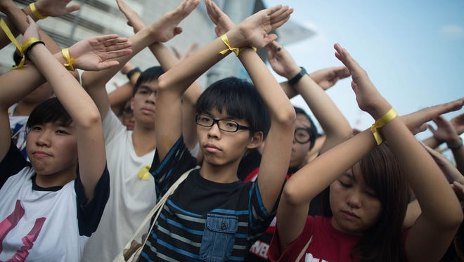 HONG KONG - OCTOBER 01:  Student pro-democracy group Scholarism convenor Joshua Wong, center, makes a gesture at the Flag Raising Ceremony at Golden Bauhinia Square on Wednesday in Hong Kong.