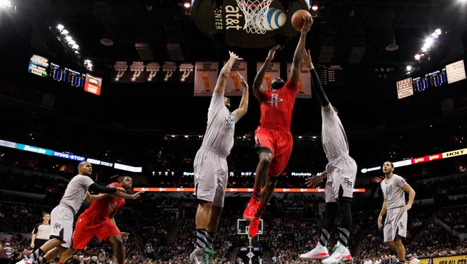 Rockets guard James Harden drives through two Spurs defenders in Wednesday's 111-98 win.