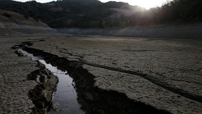 A stream of water cuts through the dry bottom of the Almaden Reservoir  on January 28, 2014, in San Jose, Calif.