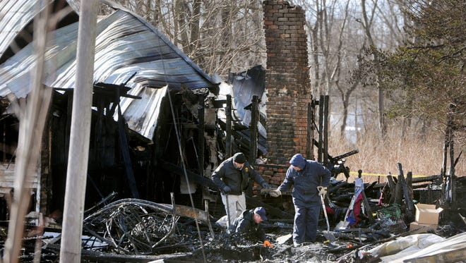 Alan Gregory, with the Kentucky Fire Marshal's office, at bottom, digs through debris Thursday Jan. 30, 2014, after a house fire that killed nine members of an 11-member family in Depoy, Ky.