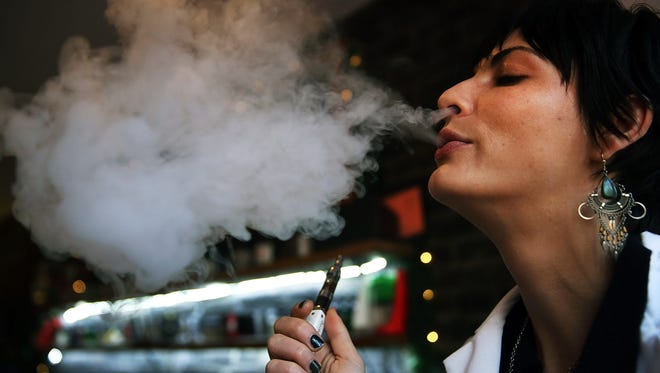 Catharine Candelario, an employee at the newly opened Henley Vaporium, vapes, or inhales from an electronic cigarette, on December 19, 2013 in New York City.