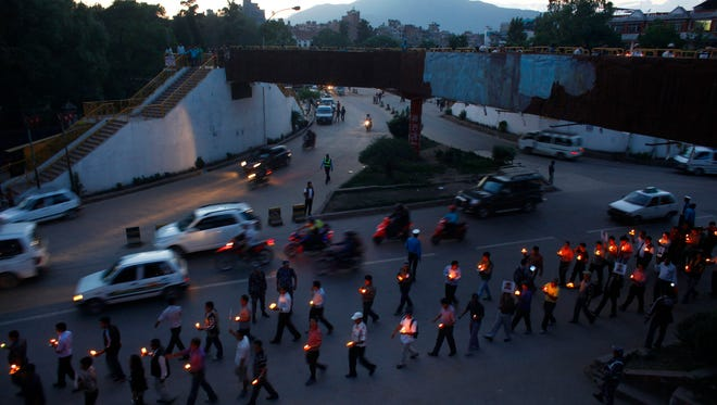 Members of Nepal mountaineers association participate in a candle light vigil on the eve of the anniversary of the conquest of Mount Everest as they remember the climbers who died in the April 18 avalanche in Katmandu, Nepal, Wednesday, May 28, 2014.