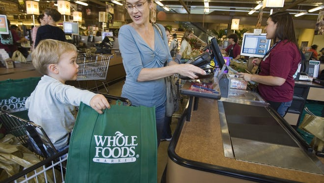 Customers shop for groceries at the Whole Foods Market in Pasadena, Calif.