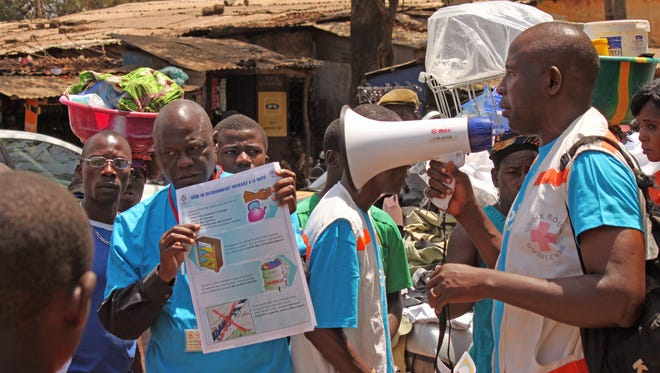 Health workers teach people about the Ebola virus and how to prevent infection,  in Conakry, Guinea, Monday, March 31, 2014. The World Health Organization last week declared the Ebola outbreak an international emergency.