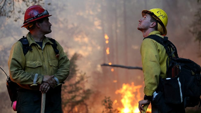 Firefighters monitor the King Fire as it burns through brush on September 17, 2014, in Fresh Pond, Calif.