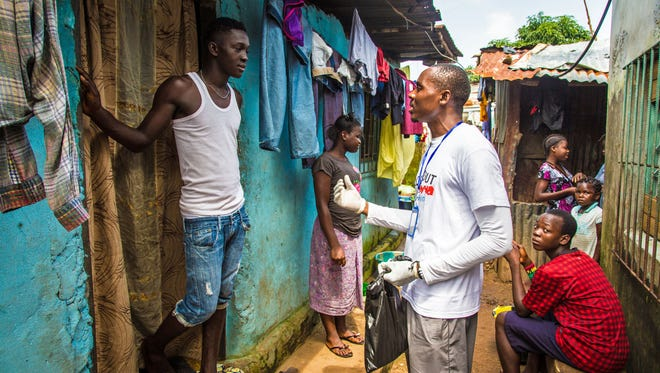 A health worker volunteer talks with a resident on how to prevent and identify the Ebola virus in others, and distributes bars of soap in Freetown, Sierra Leone, Saturday, Sept. 20, 2014. Thousands of health workers began knocking on doors across Sierra Leone on Friday in search of hidden Ebola cases with the entire West African nation locked down in their homes for three days in an unprecedented effort to combat the deadly disease.