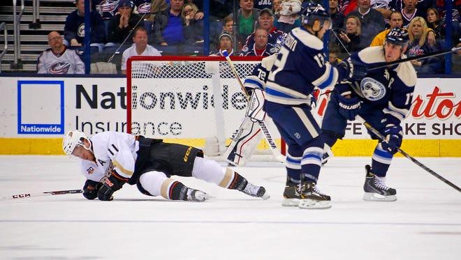 Anaheim's Saku Koivu lies on the ice after being checked by Columbus' Brandon Dubinsky.