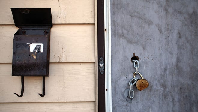 A padlock hangs from a door of a foreclosed home in Islip, N.Y.