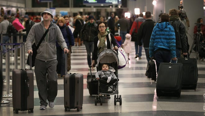 Travelers arrive for holiday flights at O'Hare International Airport on Wednesday in Chicago.