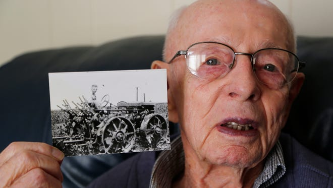 Gene Leak, 101, shows a photograph taken in 1935 of him aboard his 1930 Massey-Harris four-wheel drive general purpose tractor near Tab, Ind.