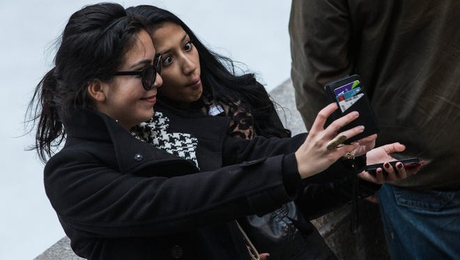 """Two women take a """"selfie"""" outside Rockefeller Center on November 19, 2013 in New York City.  Oxford Dictionary named """"Selfie"""" the new word of the year. The word is defined as """"a photograph that one has taken of oneself, typically with a smartphone or webcam and uploaded to a social media website."""""""