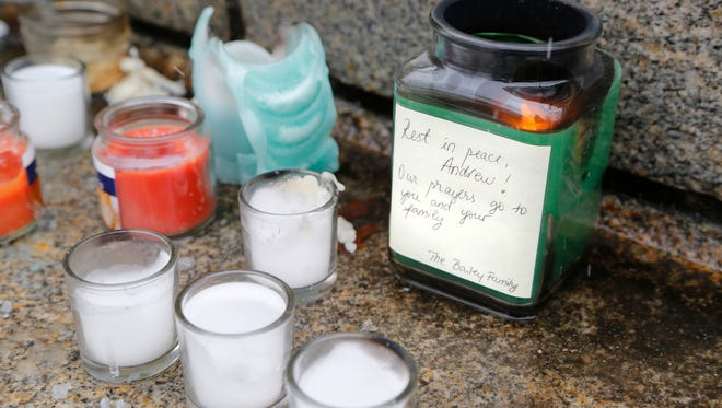 Candles, several still burning, along with flowers are placed on the steps of Hovde Hall in memorial to slain engineering student Andrew Boldt on Wednesday, Jan.  22, 2014, on the campus of Purdue University.