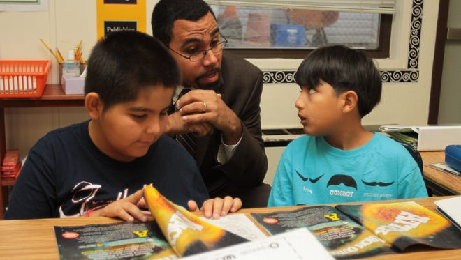 New York State Education Commissioner John King interacts with third-graders Orlando Daza, left, and Daniel Siduenza, at right, as he tours  JFK Magnet Elementary School in Port Chester Oct. 10, 2013.