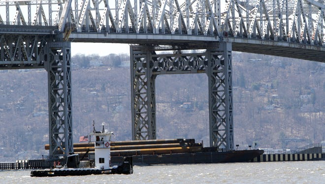 """The """"Pioneer"""" passes a construction barge that contains metal pilings at the Tappan Zee Bridge in Tarrytown March 31, 2014.  A construction barge broke from it's moorings Sunday."""