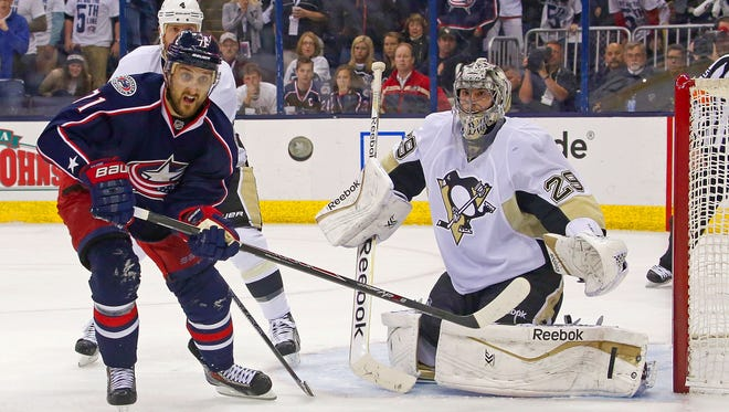 Penguins goalie Marc-Andre Fleury (29) deflects a shot as Blue Jackets forward Nick Foligno keeps his eyes on the flying puck Monday night.