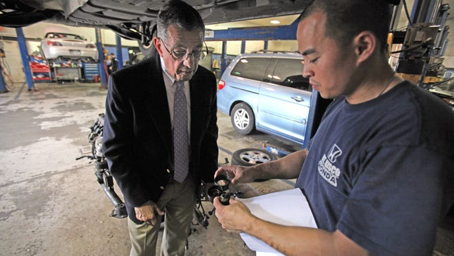 Guy Colaneri, left, general manager for Mount Kisco Honda in Bedford Hills and mechanic Ru Chen  look over failed engine parts. Colaneri hopes to take part in a clinical trial of a new drug that could help prevent Alzheimer's disease.