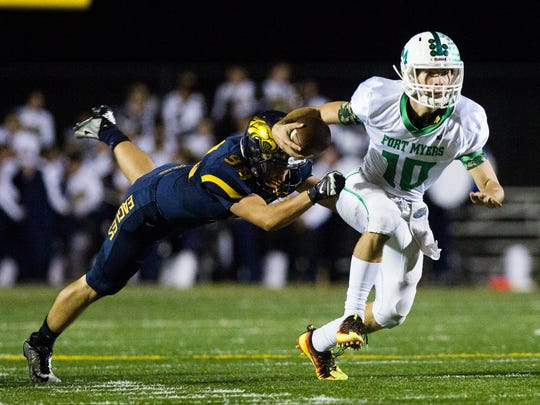 Fort Myers High School senior, Benjamin Stobugh, runs towards the end zone as Naples High School junior, Jacob Henthorne, attempts to tackle him during the Class 6A regional semifinal at Naples High School on Friday, November 18, 2016 in Golden Gate.