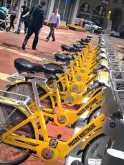 Pictured here are a yellow lineup of bikes for rent at Monument Circle for the Pacers Bikeshare program, designed as a way to use a bicycle for short trips around Downtown for a nominal rental fee. After one year of operation, the bike-share program has recorded its 100,000th rider.