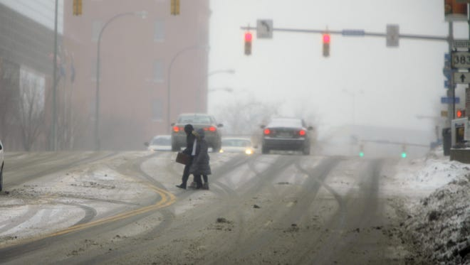 A file photo of pedestrians crossing Exchange Boulevard on a snowy afternoon in Rochester.