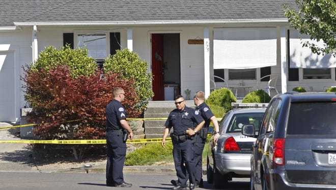 Silverton police officers at the scene of a hostage/homicide on St. Mary Circle, in Mount Angel, on Saturday, Aug. 9, 2014. Two hostages were able to escape before the shooter killed a third hostage and then taking their own life.