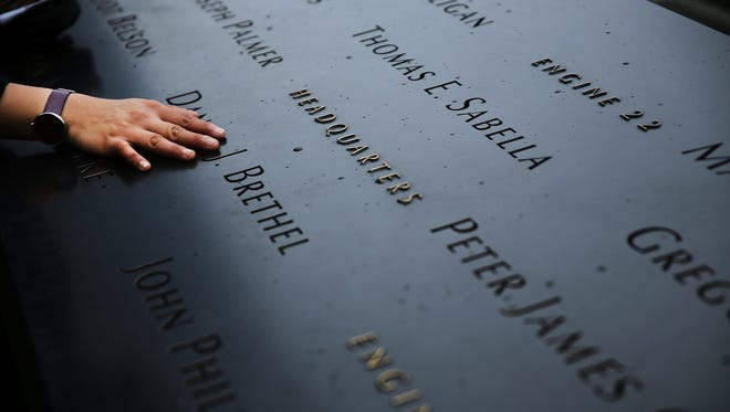 A woman places a hand on names engraved along the south reflecting pool at the 9/11 Memorial.