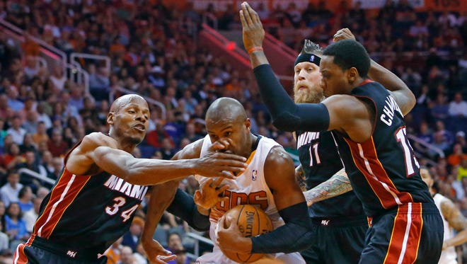 Phoenix Suns guard Leandro Barbosa (10) gets his nose bent to the side by Miami Heat guard Ray Allen (34) during the first half of an NBA basketball game Tuesday,  Feb. 11, 2014, in Phoenix.