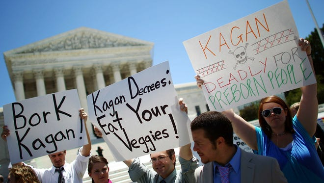Demonstrators hold signs during a protest against Supreme Court nominee Elena Kagan outside the court in 2010. Rules proposed by the Internal Revenue Service would limit the ability of tax-exempt groups to campaign for or against nominees.