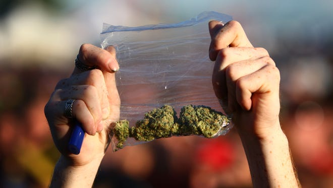 A participant holds up a bag of marijuana during the first day of Hempfest in 2011.