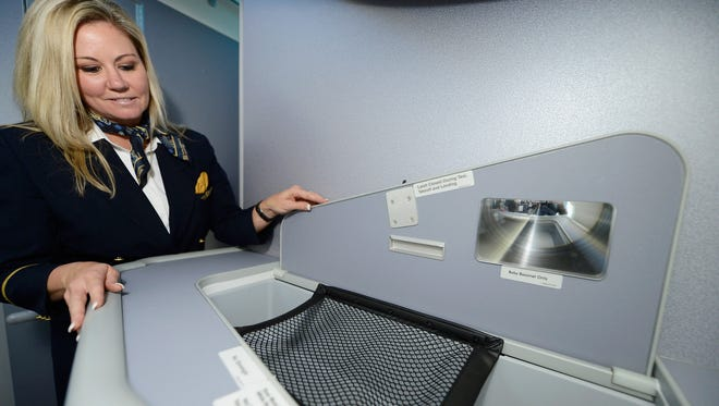 United Airlines flight attendant Tina Henderson shows the new baby bassinette while touring the new Boeing 787 Dreamliner at Los Angeles International Airport on Nov. 30, 2012 .