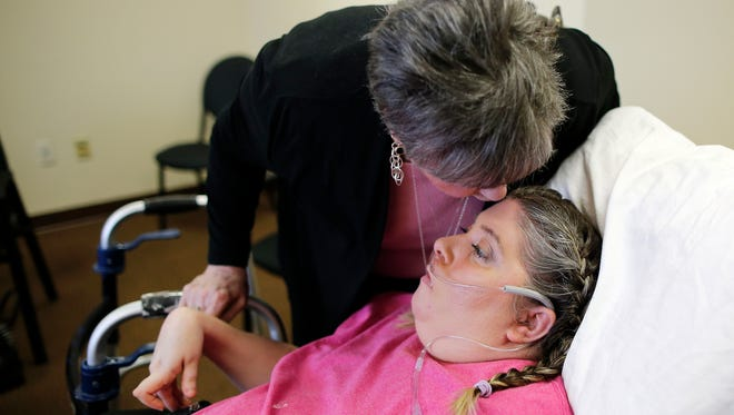 Margie Robbins kisses her daughter Melanie Robbins at a nursing home in Florence on Tuesday, April 4, 2017. Robbins was recently awarded $8.2 million in a medical malpractice lawsuit against doctors after a misdiagnosed blood vessel burst in her brain, paralyzing her and giving her brain damage.