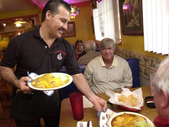 Miguel Torres serves lunch to diners at Rosita's Place in Phoenix.