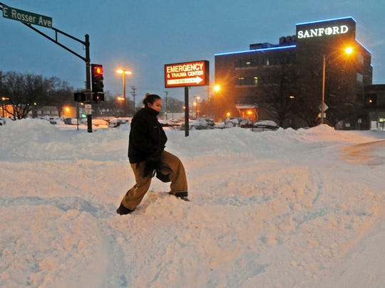 Madori Griffin, who said her car was snowed in, climbs over a snowbank to get to Sanford Hospital early Monday, Dec. 26, 2016, in Bismarck, N.D. The combination of freezing rain, snow and high winds that forced the shutdown Sunday of vast stretches of highways in the Dakotas continued into Monday morning, and authorities issued no-travel warnings for much of North Dakota.