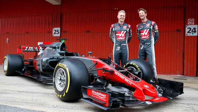 Kevin Magnussen, left, and Romain Grosjean pose with their new Haas F1 race car Monday at the at the Circuit de Catalunya in Montmelo, Spain.