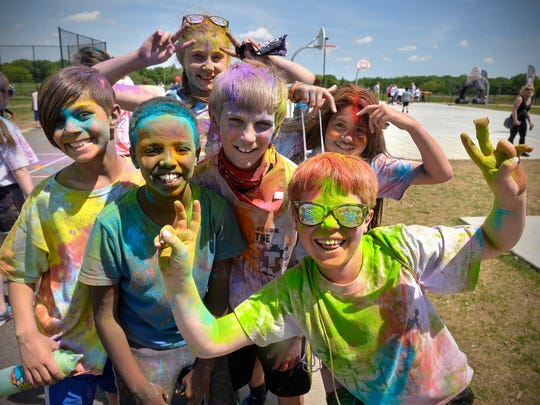 Athlos Academy students pose for a photograph after participating in the school's color-a-thon event Friday, June 2, in St. Cloud.