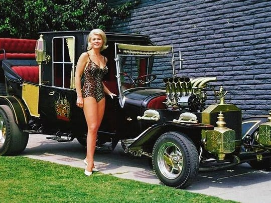 """Hot rod cheesecake: Pat """"Marilyn Munster"""" Priest poses for a promo shot with the """"Munster Koach."""""""
