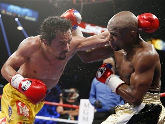 Manny Pacquiao, izquierda, lanza un golpe contra Floyd Mayweather Jr. en su pelea del 2 de mayo de 2015 en Las Vegas.  (AP Photo/John Locher, File)