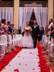 Bride Sarah Davenport makes her way down the isle in the Grand Lobby of the Cactus Hotel to meet her waiting groom.